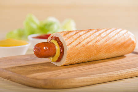 Hot Dog on a cutting board on a background of cups with ketchup and mustard.