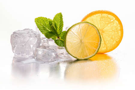 Ice cubes and slice of lime and orange with mint leaf on white background Stock Photo