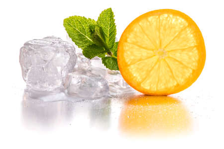 Ice cubes and slice of orange with mint leaf on white background Stock Photo