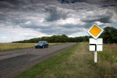 Roadway sign with a view of a car on the road photo