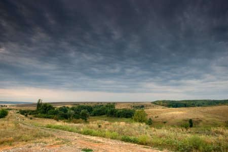 Rural road stretching out under grey clouds Stock Photo - 5838811