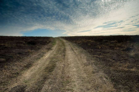 conflagration: Burnt earth after conflagration with a road stretching out to horizon Stock Photo