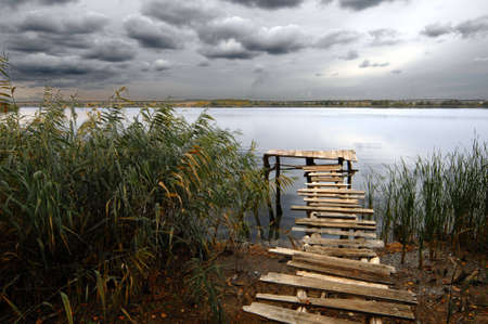 Fishing pond under stormy clouds
