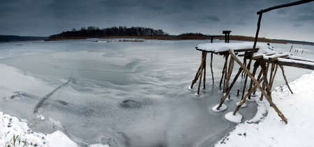 Fishing jetty on a frozen river photo