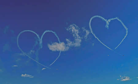 Inversion trail of the plane. A small plane makes a heart figure 스톡 콘텐츠