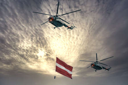 Helicopter carrying gigantic the national flag of Latvia. A military parade dedicated to the proclamation of the Republic of Latvia.