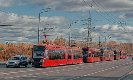 A lot of red modern city trams in Kazan. Public transportation concept. City background banner.