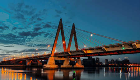 Millenium bridge in Kazan, reflected in the waters of the river Kazanka. Cable-stayed bridge across the river. The bridge with night lighting. Stock Photo