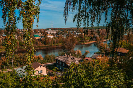 Autumn nature of Perm Krai. Kungur cityscape with houses and the Sylva River on a sunny day.