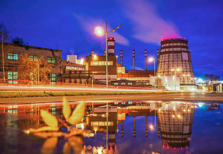 A panoramic view of the pipes and cooling towers of the CHP. Industry district at night, reflection in water.