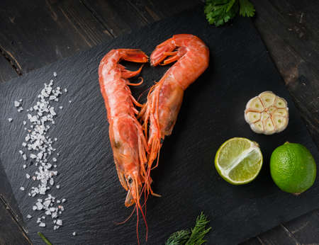 Two large langoustines with lime, salt, garlic and herbs on a black plate. Seafood healthy. Banque d'images