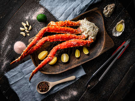 Fresh red king crab crab claws with lemon slices and spices . Tasty kamchatka crabs claw