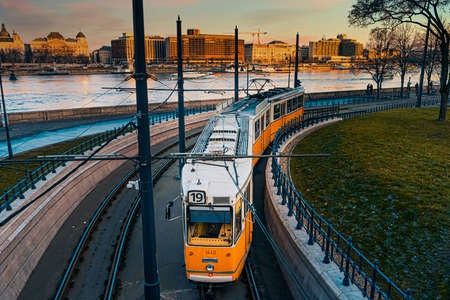 A yellow tram travels along the banks of the Danube. Sunset view.