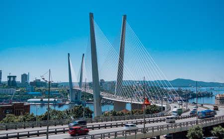 The bridge across the Golden horn bay in Vladivostok in sunny weather. Golden Bridge and view of Vladivostok