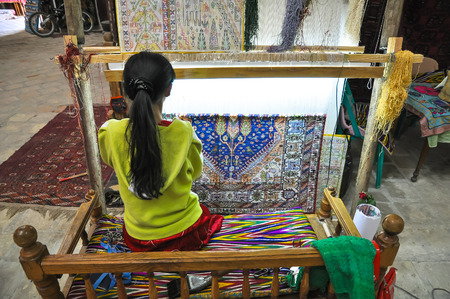 handloom: Young woman weaves a carpet on handloom. Stock Photo