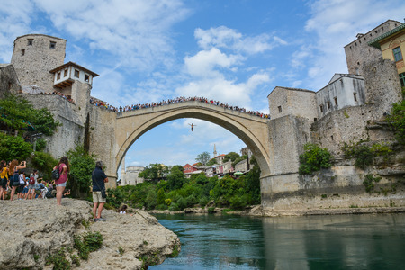 Man jumping from a very high ancient bridge in Mostar. Stock Photo