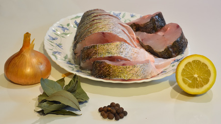 pikeperch: Sliced fish on a plate, onion, pepper, laurel leaf, lemon.
