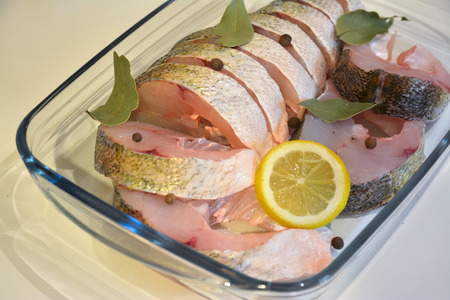 pikeperch: Appetizing sliced fish in a glass tray with the spices.