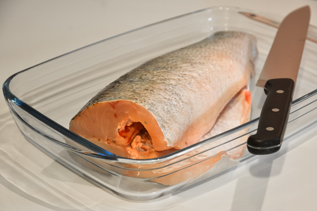 purified: Purified fish for cooking in a glass tray and knife.
