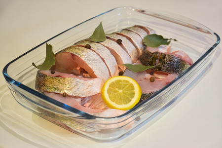 pikeperch: Sliced fish in glass tray with spices. Stock Photo