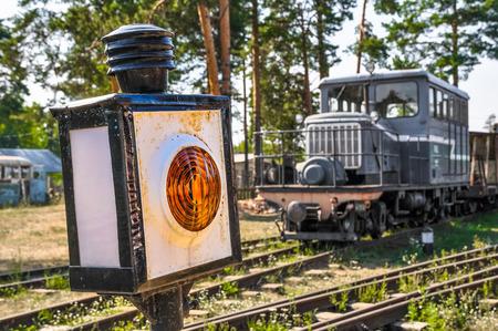 narrow gauge railroads: Yellow semaphore and the locomotive on the railway.