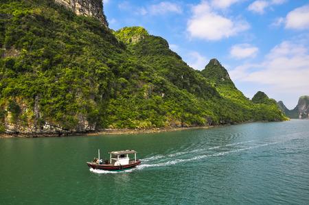 halong: Small motor boat races among the islands of Halong Bay. Stock Photo
