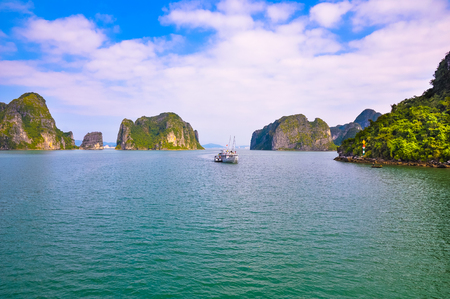 halong: Tourist boat in Halong Bay sailing among the islands.
