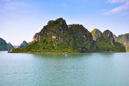 halong: Many rocky islands covered with vegetation in Halong Bay.