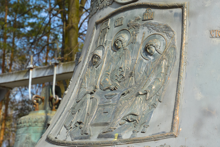 sacred trinity: Image of three angels on the large bell. Stock Photo