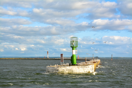 navigational light: Long concrete pier with a lighthouse and a lot of gulls. Stock Photo