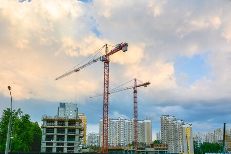Cranes are on the construction site of residential buildings.