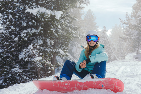 Snowboarder in the mountains. Girl on a snowboard comes down from the mountain. Stock Photo