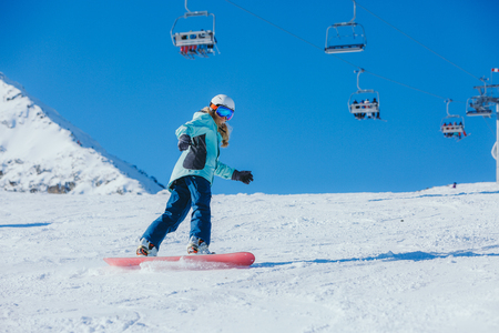 Snowboarder in the mountains. Girl on a snowboard comes down from the mountain. Stockfoto