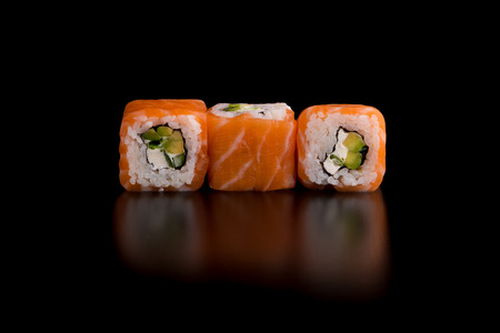 Japanese traditional food - sushi with avocado, rice, cottage cheese, salmon and green onion on the black background.