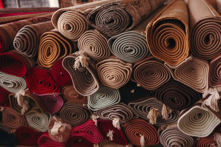 A stack of folded carpets of different colors, which can be seen in a carpet store in Dubai Stockfoto