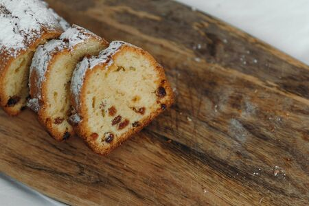 Raisin cake, dusted with icing sugar. Cupcake with raisins on a wooden board