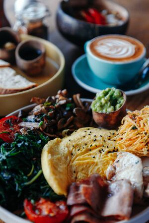 Morning breakfast on a table, waffles with cream, berries, coffee, cappuccino, bowl, omlet with vegetables, bread with butter, avocado cream, vegan food, healthy food, meal.