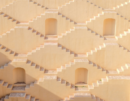 Four recessed doorways & cream-colored zigzag stairs of Panna Meena Ka Kund, a 8-story step-well near Amber Fort in Jaipur, India