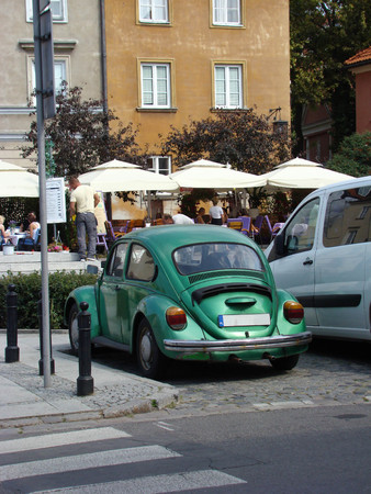 Old green Volkswagen Beetle parked on one of the streets of Warsaw (Poland) Editorial