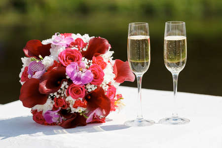 two glasses of sparkling wine and bouquet of the bride. Imagens