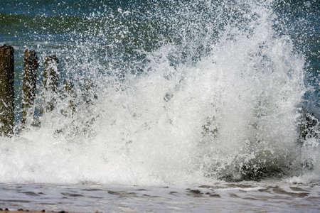 breaking: sea waves breaking on breakwater Stock Photo