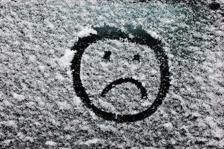 snowcovered: sad smiley face drawn on snow-covered glass