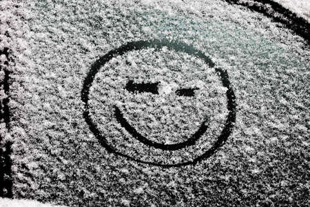 face close up: a smiley face drawn on snow-covered glass