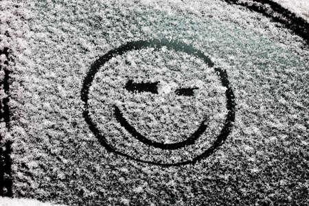 cara sonriente: una cara sonriente dibujada sobre el vidrio cubierto de nieve