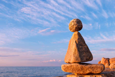 Concept of harmony and balance. Rock Zen at sunset