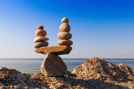 equipoise: Concept of harmony and balance. Balance stones against the sea. Rock zen in the form of scales
