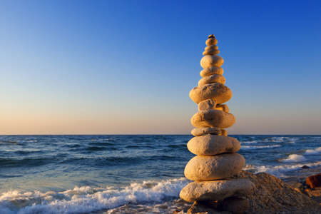 exactness: Concept of harmony and balance. Rock Zen at sunset. Balance and poise stones against the sea Stock Photo