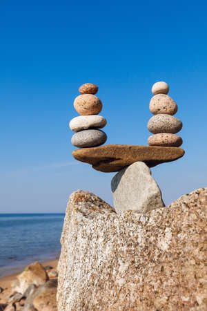 equipoise: Concept of harmony and balance. Balance and poise  stones against the sea. Rock zen in the form of scales