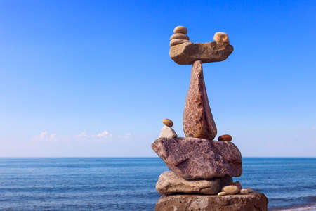sameness: Concept of harmony and balance. Balance and poise stones against the sea. Rock zen in the form of scales