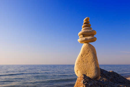 poise: Concept of harmony and balance. Rock Zen at sunset. Balance and poise stones against the sea Stock Photo
